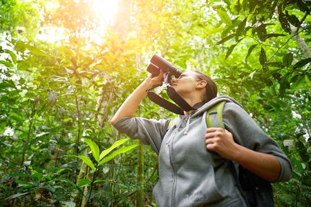 Young female hiker watching through binoculars wild birds in the jungle. Bird watching tours