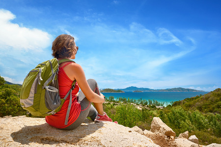 Young tourist with backpack relaxing on top of the mountain and enjoying beatiful coast view. Ecotourism concept image with happy female hiker.