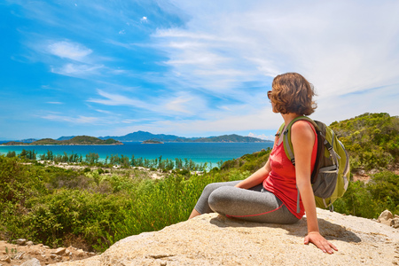 women sport: Tourist with backpack standing on a rock on clear sky background looking at beautiful landscape motivation and inspiration.