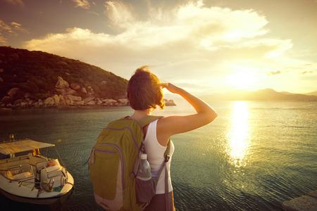 젊은 여자 등산객 해안에 서 바다 위로 일출 즐기고있다. 아시아 활동적인 라이프 스타일의 개념을 따라 여행