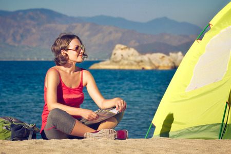 trekker: Young lady hiker sit near the tent and looking on sea landscape. Traveling, freedom and active lifestyle concept