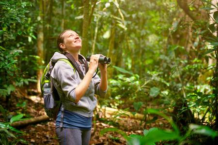 jungla: Caminante mirando a través de binoculares aves silvestres en la selva. Observación de aves excursiones
