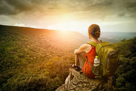 Young woman hiker sits on the edge of the cliff and enjoying sunrise looking at the valley and mountains. Traveling along Asia, active lifestyle concept Archivio Fotografico