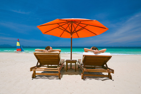 sun umbrella: Couple on a tropical beach relax in the sun on deck chairs under a red umbrella.  Travel  background.