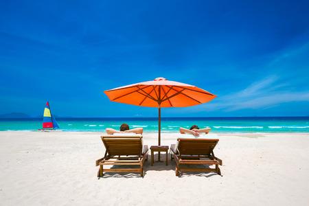 Paar op een tropisch strand ontspannen in de zon op het dek stoelen onder een rode paraplu. Reizen achtergrond.