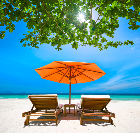 travel background: Two deck chairs under a red umbrella on  tropical beach. Travel  background.