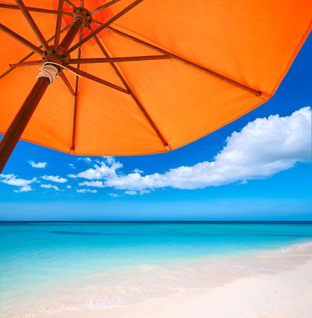 Rode paraplu op tropisch strand. Reizen achtergrond.