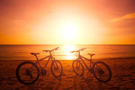 travel background: Two bike silhouette at the sunset near sea. Travel background