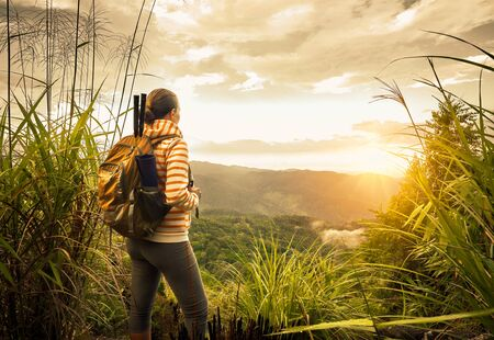 top mountain: Woman backpacker traveling  with backpack standing on top of the mountain and enjoying sunrise view