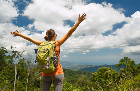 Woman traveler with backpack enjoying mountains view with raised hands .