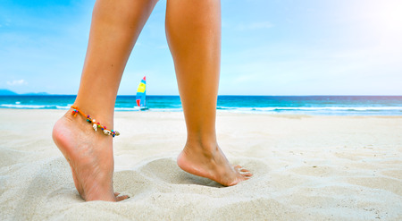 sandy feet: Beach travel - young female legs one bracelet on sandy beach