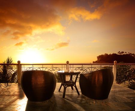 전망: 럭셔리 리조트에서 등나무 안락 의자와 바다 전망과 테라스 라운지. 여름 휴가 개념