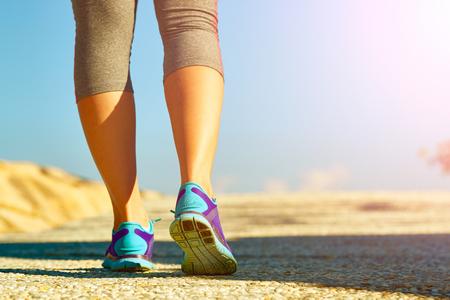 Runner nohy běží na silnici detailní na boty. Žena fitness jog cvičení wellness koncept.