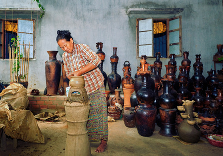 ollas de barro: Thun provincia de Ninh, Vietnam - 2 noviembre 2014: Un pueblo de cerámica Bau Truc, mujer crea olla de barro artesanía tradicional en Vietnam. Utilizando técnicas tradicionales