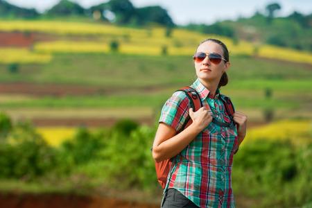 mochila de viaje: Retrato de niña viajero con mochila de pie en en el fondo de los campos de color y disfrutar de vistas al valle. Viajar, la libertad y el concepto de estilo de vida activo. Foto de archivo
