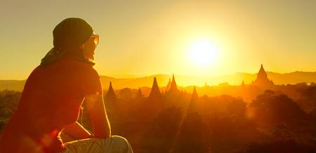 Mladý batohem se těší chrámů v Bagan Myanmaru Asii při západu slunce pohled z vrcholu chrámu.