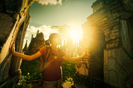Traveler with a backpack looks at sunset ancient Buddhist stupa of the temple complex In Dein, Inle Lake. Mayanmar Banco de Imagens