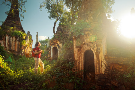 Backpacker traveling with backpack and looks at sunset ancient Buddhist stupa of the temple complex In Dein, Inle Lake. MayanmarTraveling along Birma, freedom and active lifestyle concept