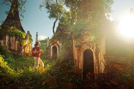 Backpacker reizen met rugzak en ziet er bij zonsondergang oude boeddhistische stoepa van de tempel complex In Dein, Inle Lake. MayanmarTraveling langs Birma, vrijheid en actieve lifestyle concept Stockfoto