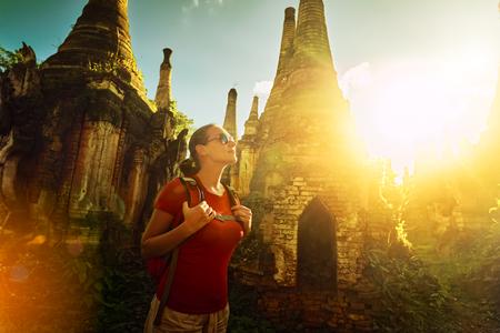 mochila de viaje: Backpacker de la mujer que viaja con mochila y se ve al atardecer entre la antigua estupa budista del complejo del templo En Dein, Lago Inle. MayanmarTraveling junto Birma, la libertad y el concepto de estilo de vida activo