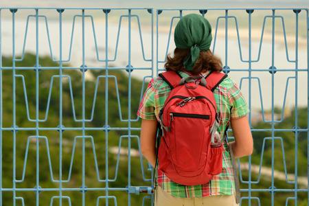 mochila de viaje: Un viajero con una mochila mirando a través de la valla de metal en el área cerrada para visitar.