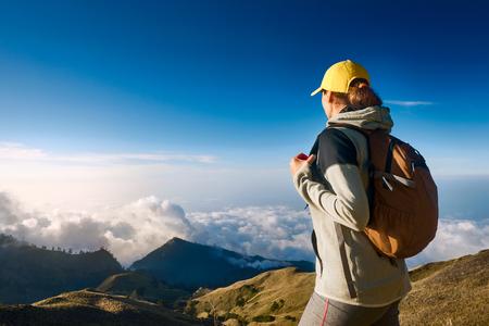 Turista se dívá na výhled ve vysokohorských horách nad mraky. Žena s batůžkáři s výhledem na vrchol vrcholu ve vysokých horách.