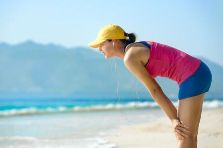 agotado: La mujer Athletic de descanso después de trotar. Cansado agotado atleta femenina en forma de tomar un descanso, respirando con dificultad después de correr en la playa. Entrenamiento, ejercicio. Concepto de la salud, estilo de vida saludable.