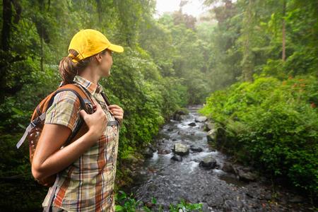 Mladá žena turista s batohem stojící a těší deštného pralesa a výhledem na řeku. Lombok, Indonésie. Turista turistika v hluboké džungli