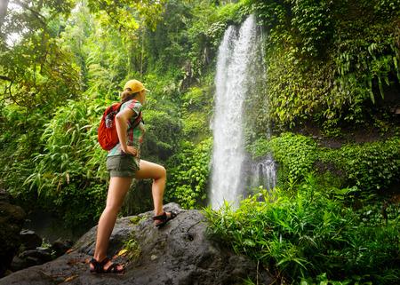Mladá žena batohem pohledu na vodopádem v džungli. Ekoturistika pojetí obrazu cestovní dívka