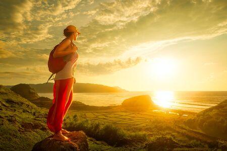 Un jeune voyageur regardant le coucher du soleil sur l'île de Lombok, Indonésie. Voyager le long de l'Asie, le concept de mode de vie actif Banque d'images