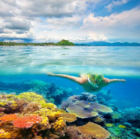 Mladá žena koupání na korálový útes v moři na pozadí tropické pláži. Lombok, Indonésie