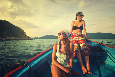 Two young woman traveling by boat at sunset among the islands
