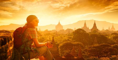 Unga resenären åtnjuter en titta på solnedgången på Bagan, Burma Asien. Färdas längs Asien, aktiv livsstil koncept
