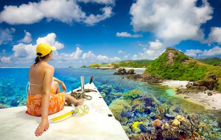 女性旅行者がインドネシア ・ ロンボク島周辺の珊瑚礁を楽しむボートの帆します。