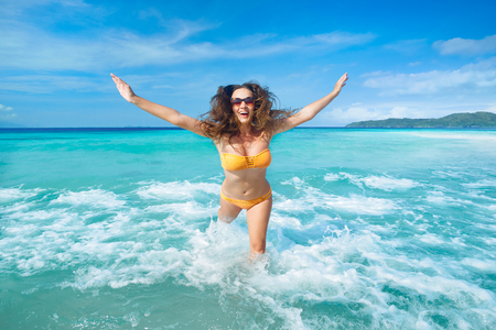 exhilarated: Cheerful young woman with flying hair running on beach fun laughing during summer holidays travel. Beautiful tourist is enjoying vacation on beach.