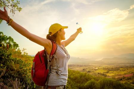 Portrait eines glücklichen Reisenden mit Rucksack und eine Flasche Wasser auf dem Gipfel des Berges stehen und Blick auf das Tal mit erhobenen Händen zu genießen. Berge Landschaft, Reisen nach Asien, Glück Emotion, Sommerferien Konzept Standard-Bild