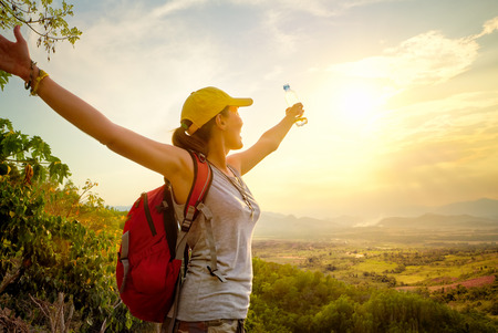 Portrait of happy traveler with backpack and a bottle of water standing on top of the mountain and enjoying valley view with raised hands.