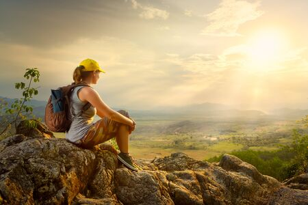 Portrait of happy woman with backpacker sitting on top of the mountain and enjoying sunset and valley view.
