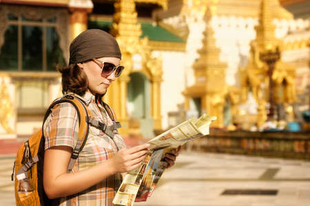 buddhist's: Woman traveling with backpack and looks at map temple Buddhist Shwedagon Pagoda . Myanmar