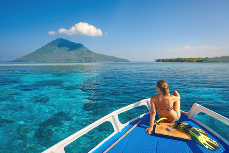 Young woman in swimsuit sit on boat at sunny day looking to a clean sea and volcano Manado Tua.North Sulawesi, Indonesia.