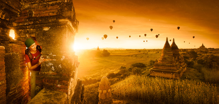 explores: Woman traveler with a backpack explores the ancient temple on a background of beautiful sunrise with balloons. Bagan, Myanmar.Traveling along Asia, active lifestyle concept. Stock Photo
