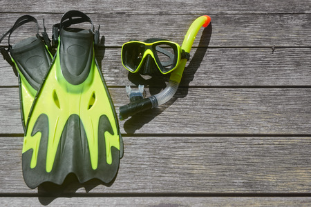 snorkelling: Scuba diving and snorkelling. Flippers, mask, snorkel on wood brown background Stock Photo