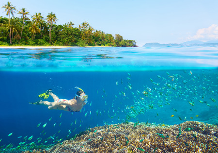Young woman swimming above bright coral reef in the sea on a background of a tropical beach