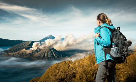 discovering: Young woman backpacker enjoying view volcano Bromo,  island, Indonesia. Discovering world, summer vacation concept.