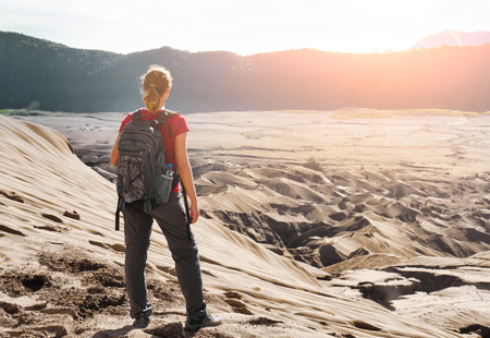 discovering: Young woman backpacker traveling along mountains and desert, female walking  discovering world, summer vacation concept