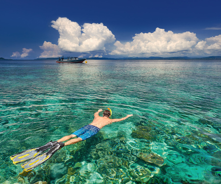 Young man snorkeling in clear tropical waters over coral reefs on a background of exotic islands and boat.North Sulawesi, Indonesia. Stock Photo