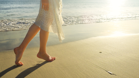 Young girl in white dress walking alone on the sandy beach at sunrise.Closeup detail of female feet and golden sand on beach.