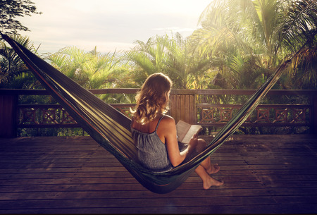 Young woman reading a book in a hammock on the terrace in the jungle at sunset