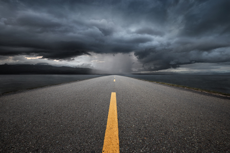 Empty highway leading to the mountains through the rain on a background of dark storm clouds