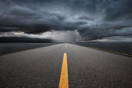 Leere Autobahn, die in die Berge durch den regen auf einem Hintergrund des dunklen Gewitterwolken